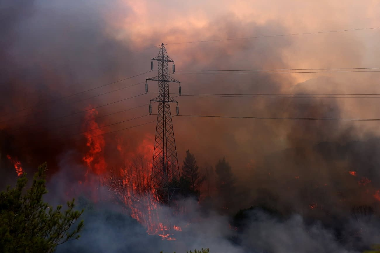 Varibobi, 2021. augusztus 3. Lángol a növényzet Athén északkeleti külvárosa, Varibobi környékén 2021. augusztus 3-án. 350 tűzoltó, 70 járművel, öt helikopterrel és kilenc repülővel próbálja oltani a tüzet, amely egyelőre nem fenyeget lakóépületeket, ipari létesítményeket, de vastag füstfelhővel borítja be a város légterének egy részét. Görögországban, ahol 42 Celsius-fokos hőség tombol, több mint száz helyen kapott lángra a növényzet az utóbbi napokban. MTI/EPA/ANA-MPA/Oresztisz Panajotu